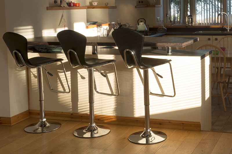 A view of the kitchen bar with 3 stools