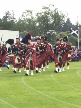 A marching band dressed in red tartan with bagpipes