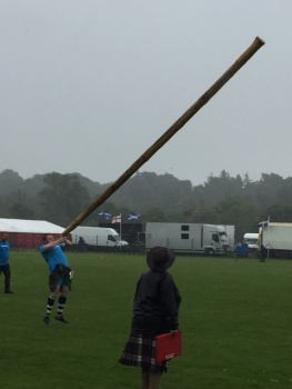 An athlete tossing the caber, a very long heavy piece of wood